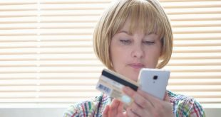 woman does shopping online from her phone with card in hand