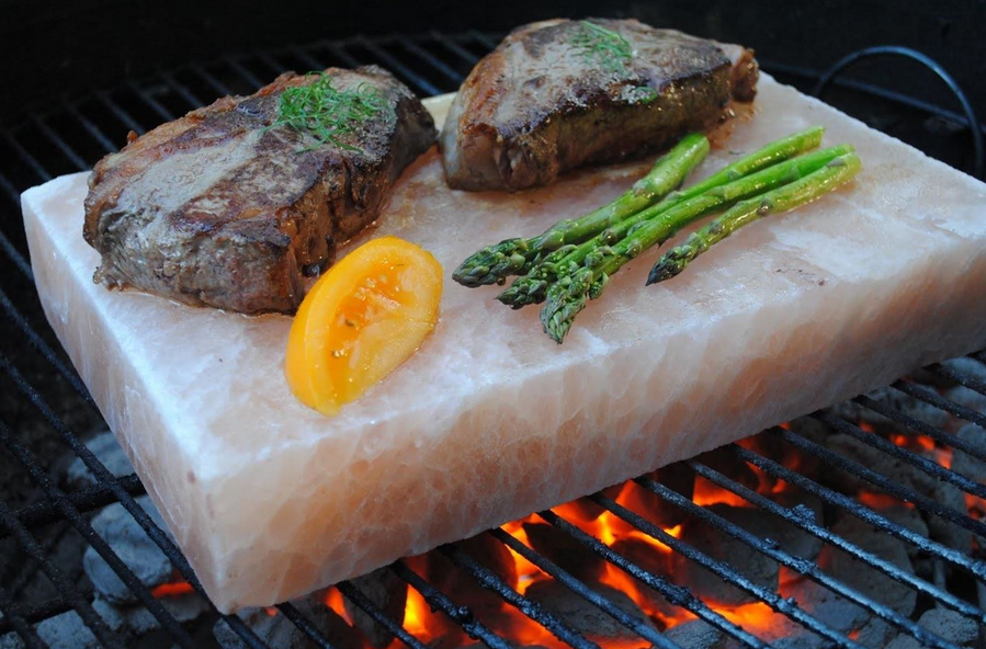 salt slab on grill with steaks tomato slice and asparagus