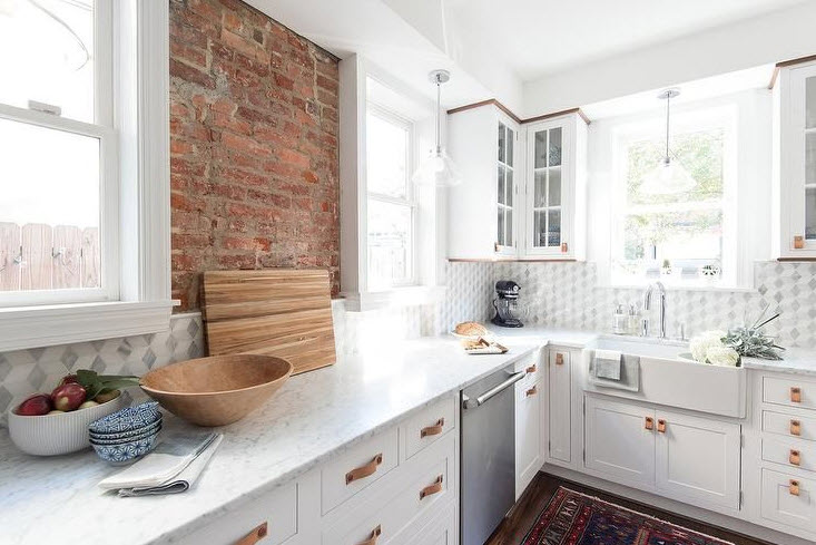 white cabinets with brick wall
