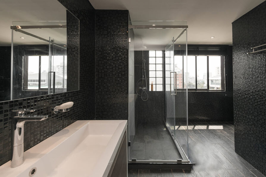modern bathroom with glass shower panels black tiles and long white square ceramic sink