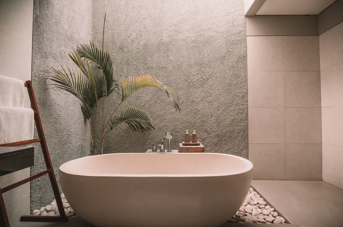 oval shaped bathtub on an area covered with white stones in cream bathroom