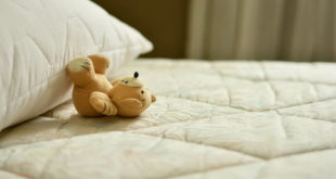pillow and teddy bear on well taken care of mattress
