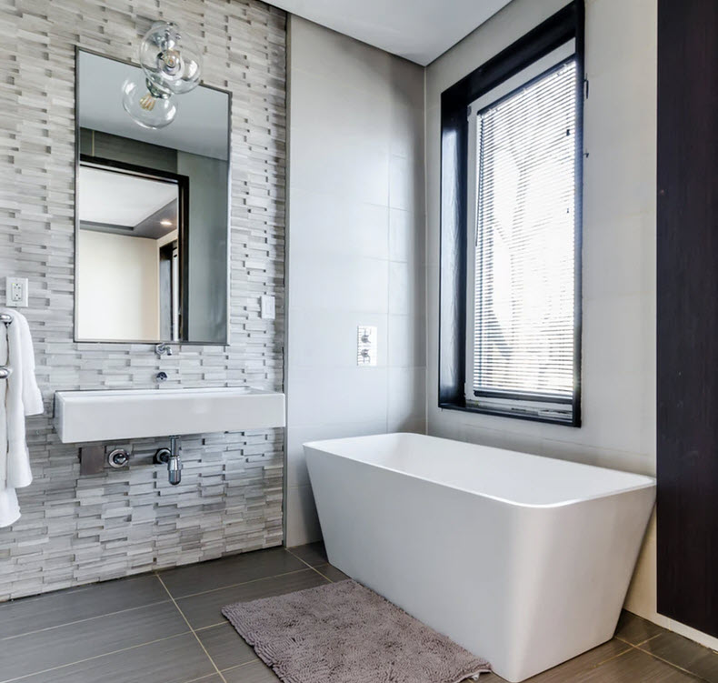 white ceramic bathtub near white framed window and apparent stone mirror sink wall