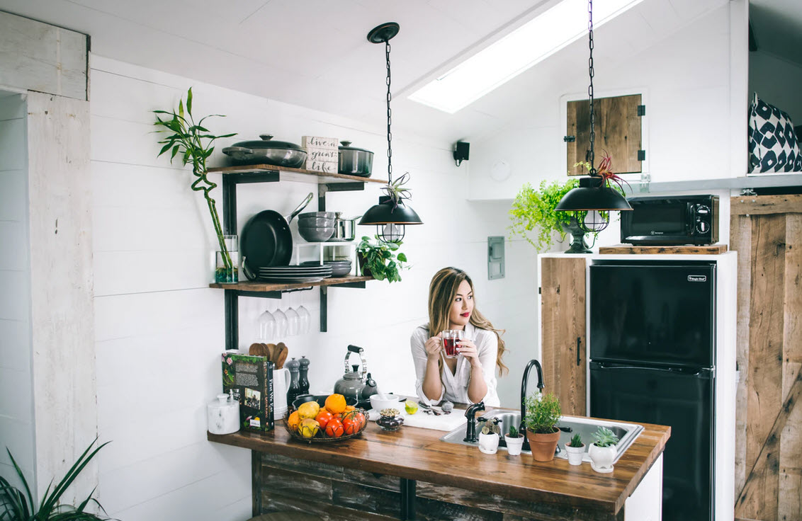 young woman in her custom designed kitchen with modern white and rustic wood