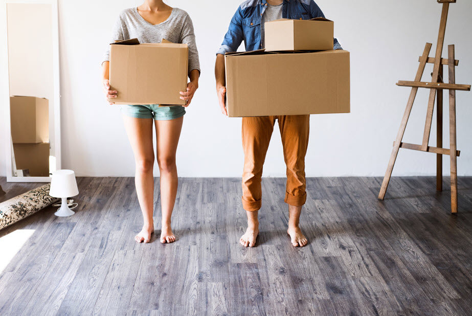 couple moving in with boxes in hands