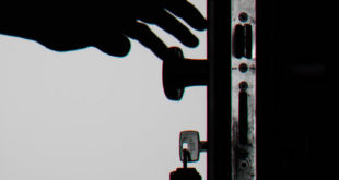 hand on door knob opening door keys in lock